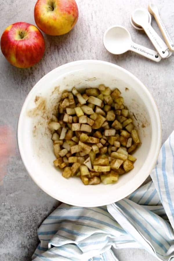 bowl with cut up apples that have been tossed in cinnamon