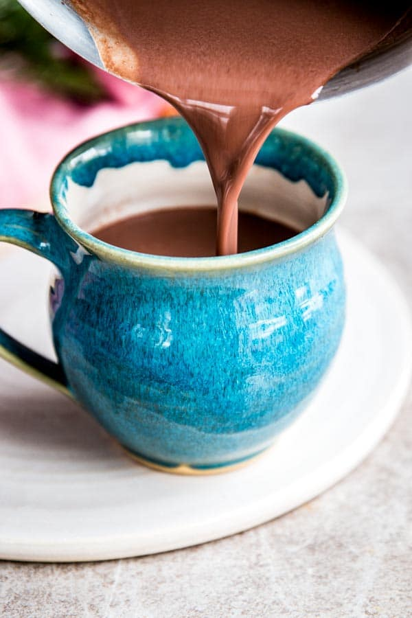 Pouring homemade hot chocolate into a pottery mug.