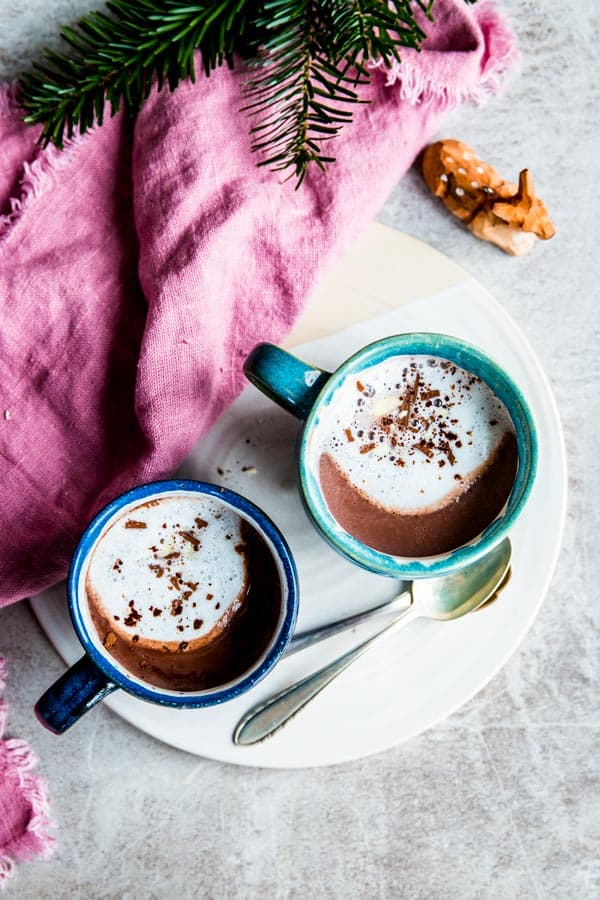Two mugs of hot chocolate in a Christmas scene.
