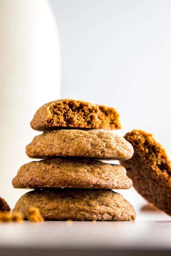stack of molasses cookies in front of a milk bottle