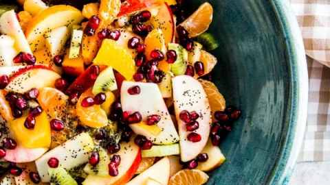 overhead photo of winter fruit salad in blue bowl