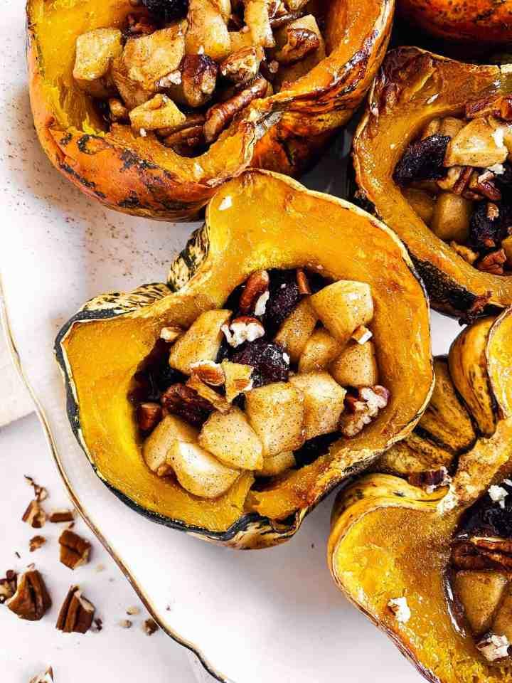 close up photo of stuffed acorn squash on white platter