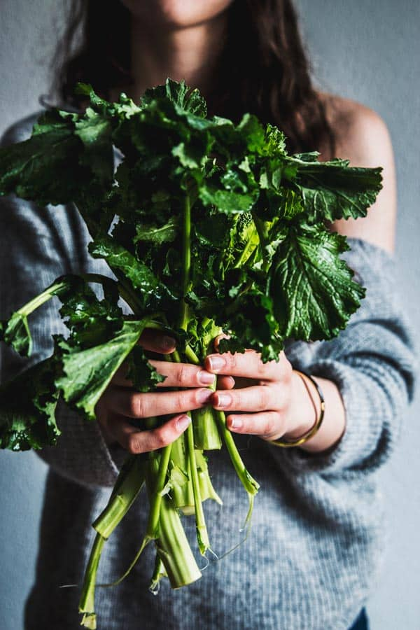 Woman in grey knit pullover, holding stems of broccoli rabe.