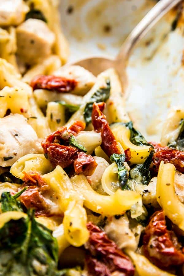 Close up photo of Chicken Florentine Pasta Casserole with sun-dried tomatoes, chicken and spinach.