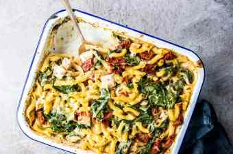 Chicken Florentine Pasta Casserole in a enamel casserole dish with a silver spoon.