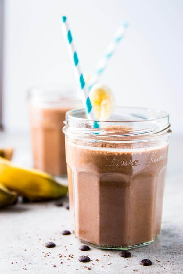 Two glasses of chocolate peanut butter banana smoothie with paper straws