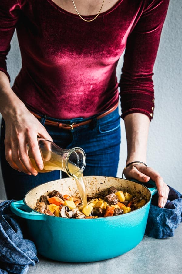 Woman pouring beef stock into beef stew in a Dutch oven.