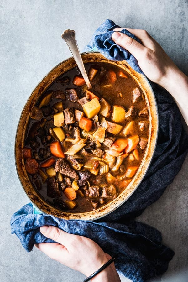 Woman holding a large oval Dutch oven filled with Guinness Beef Stew.