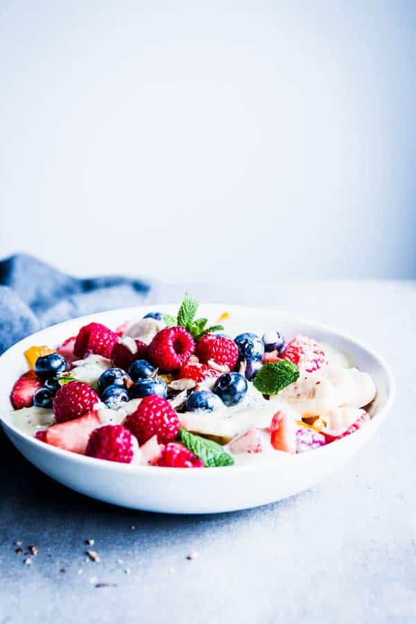 Creamy fruit salad in a white bowl on the table.