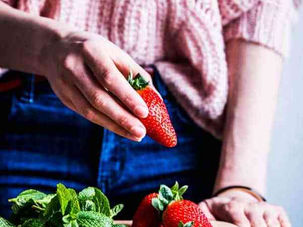 Woman in a pink sweater holding a strawberry.