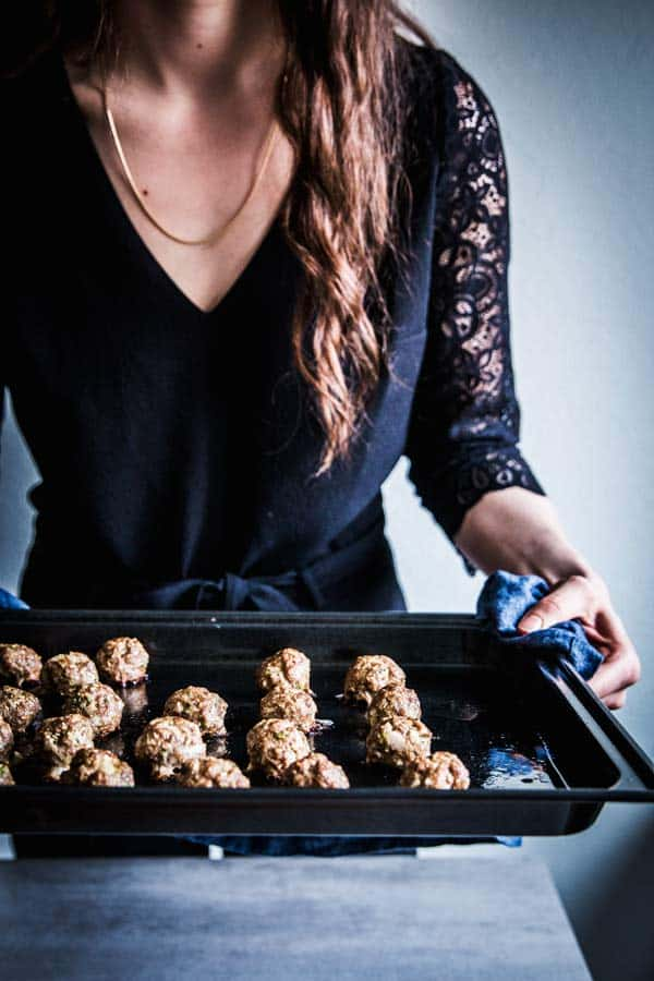 Woman in a black jumpsuit, holding a sheet pan with baked meatballs.