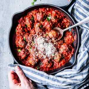Serving easy Italian meatballs in tomato sauce from a black cast iron skillet.