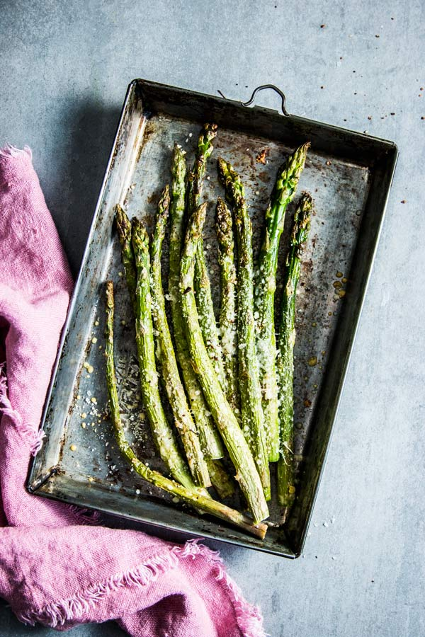 Parmesan Roasted Asparagus on a metal sheet pan with a pink napkin.