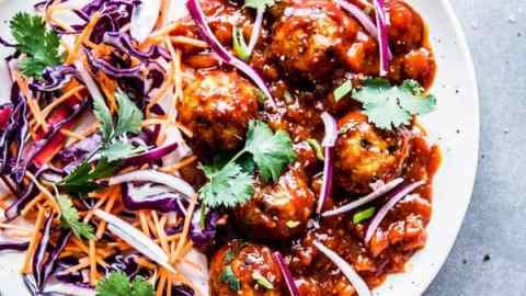 Pineapple BBQ Meatballs on a white plate with slaw and cilantro.