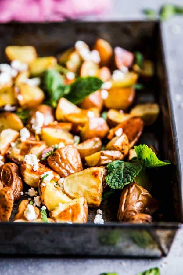 Roasted red potatoes with feta and mint on a baking sheet with a pink napkin, close up photo.