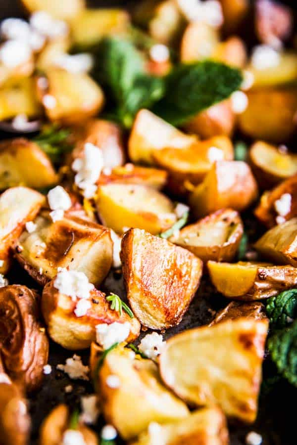 A close look at roasted red potatoes with feta and mint on a baking sheet with a pink napkin.