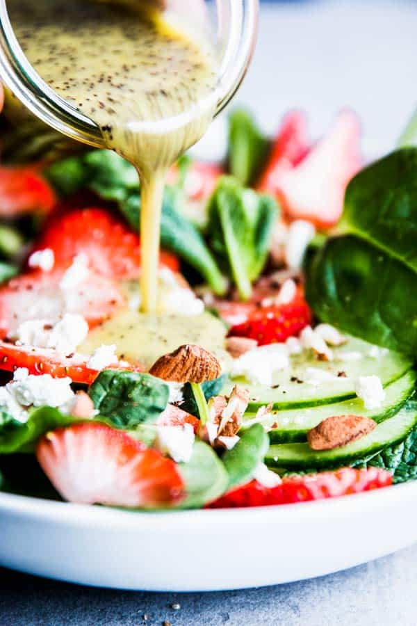 Pouring lemon poppy seed dressing over strawberry spinach salad.