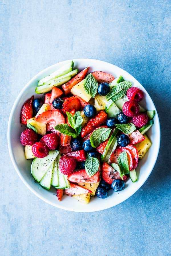 Summer fruit salad in a white bowl.