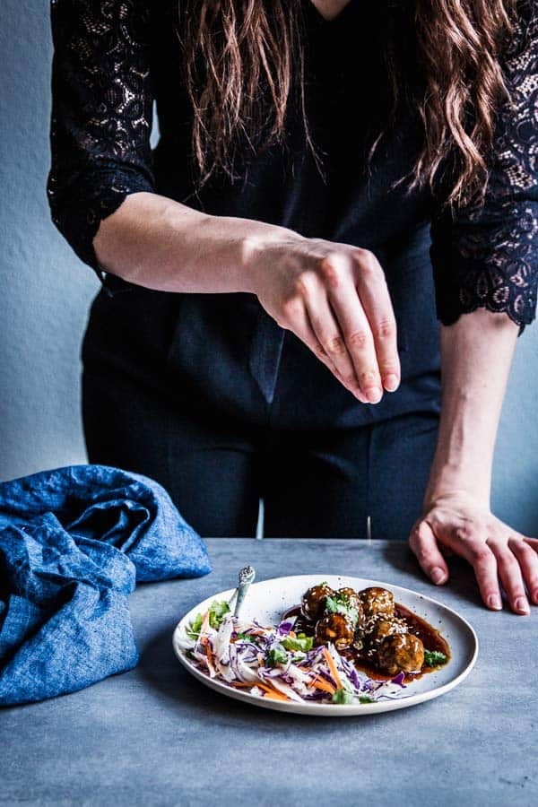 Woman sprinkling sesame seeds on a plate of teriyaki meatballs and coleslaw.