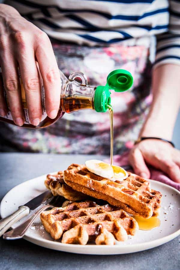 Woman in a striped top pouring maple syrup over banana nut waffles.