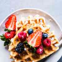 Stack of buttermilk waffles on a white plate with cutlery and berries.
