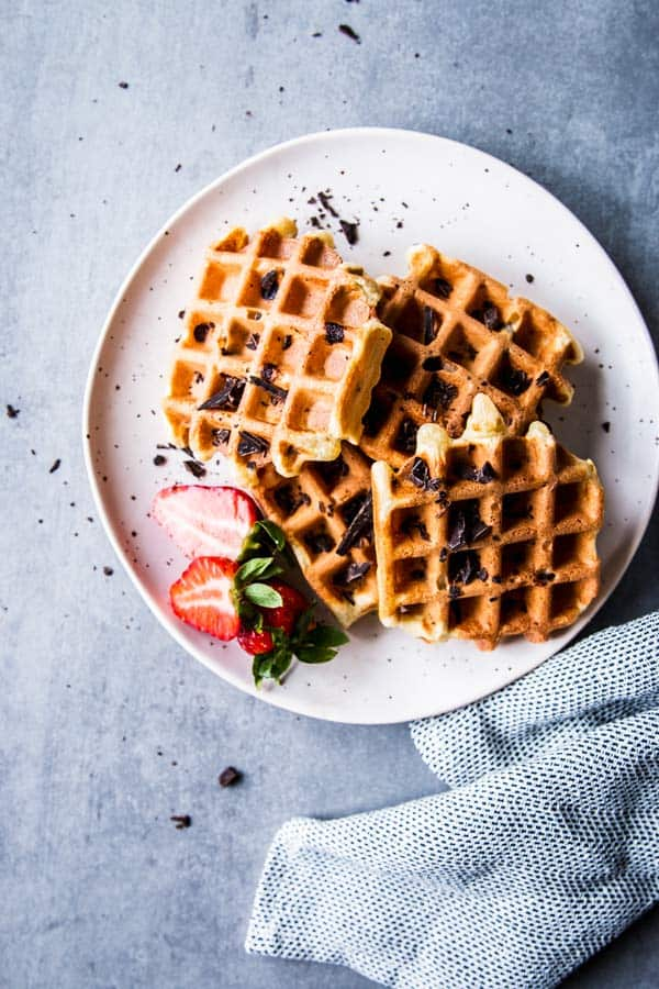 Chocolate Chip Waffles on a white plate with a light napkin and some strawberries.