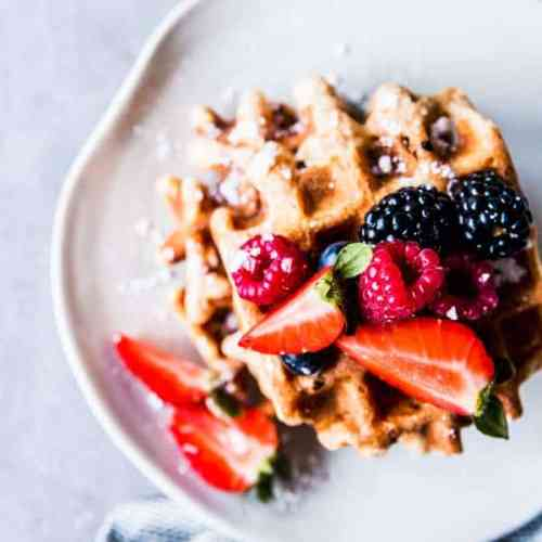 Fluffy Whole Wheat Waffles on a white plate with fresh berries.
