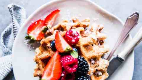 Fluffy Whole Wheat Waffles on a white plate with berries.