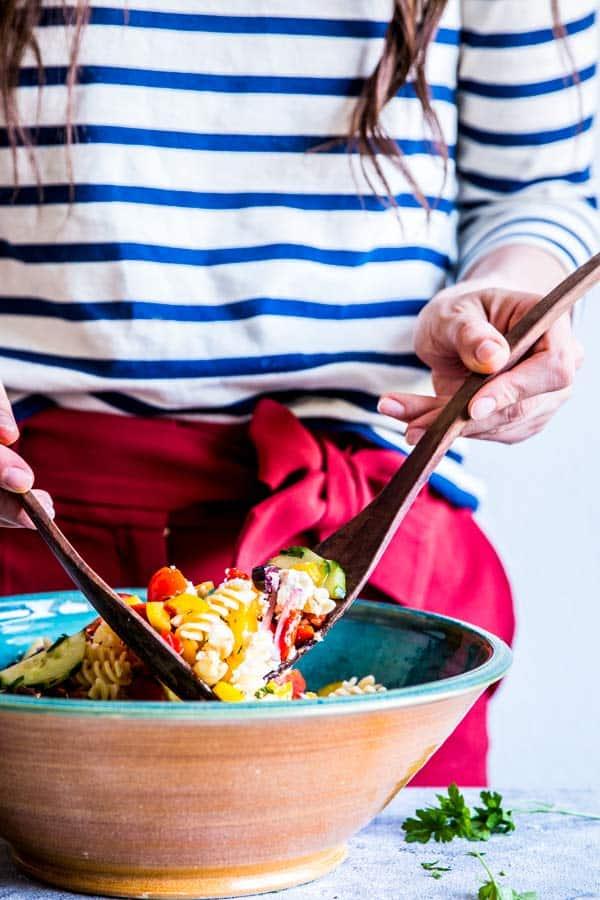 woman mixing a bowl of greek pasta salad