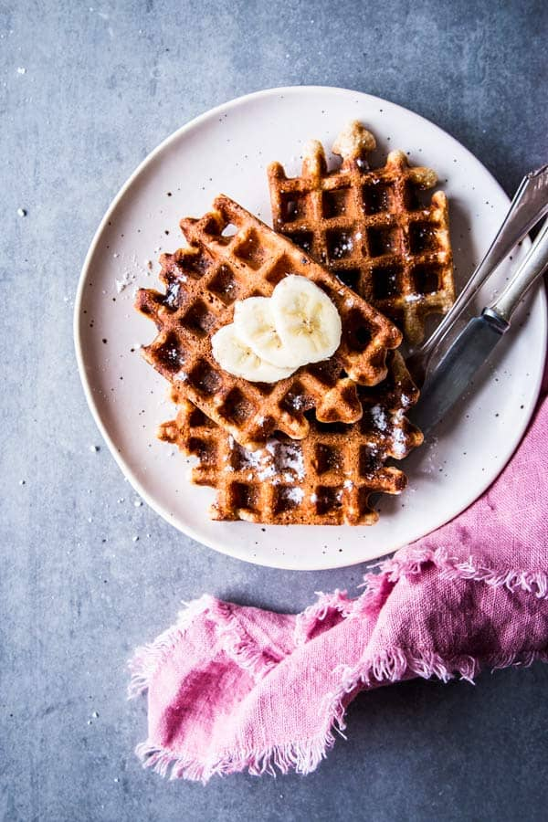Healthy Banana Waffles on a white plate with a pink napkin.