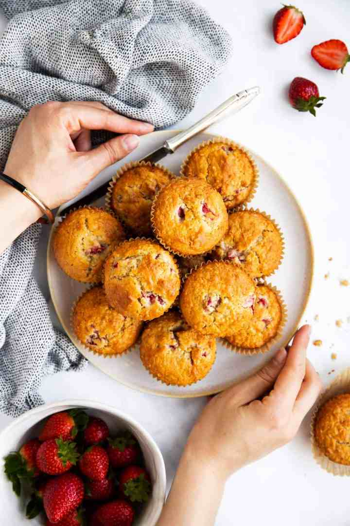 female hands holding a plate with strawberry oat muffins