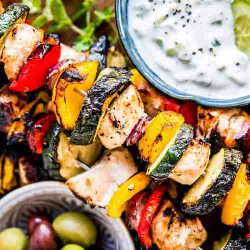 greek chicken kabobs on a platter with tzatziki and olives