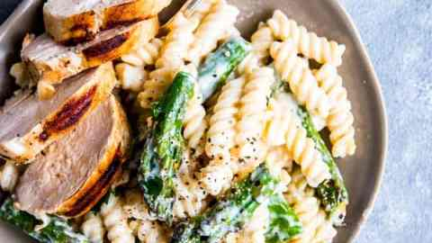 Chicken Asparagus Pasta on a light plate with a fork and some herbs