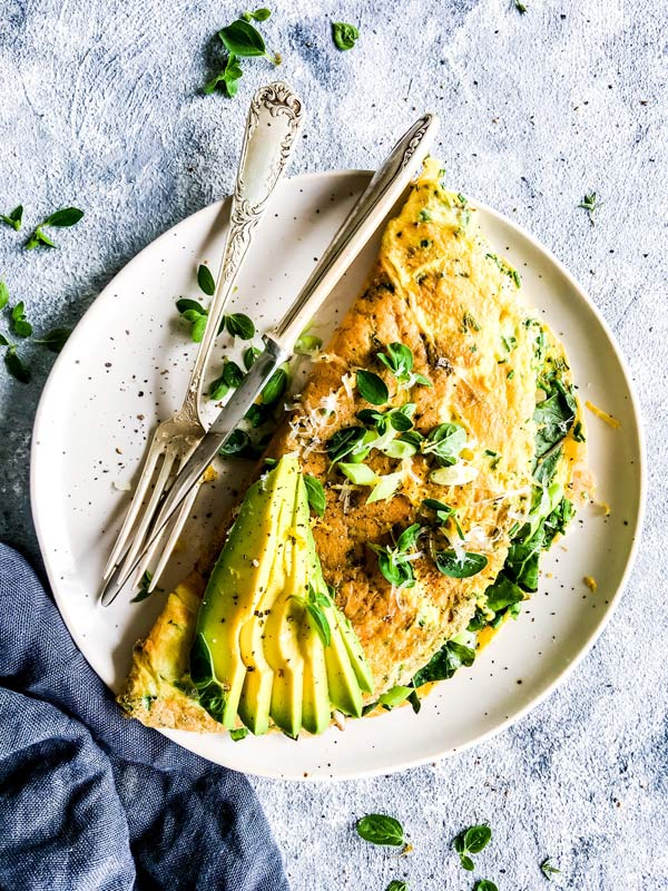 green goddess omelette on a white plate with herbs and avocado