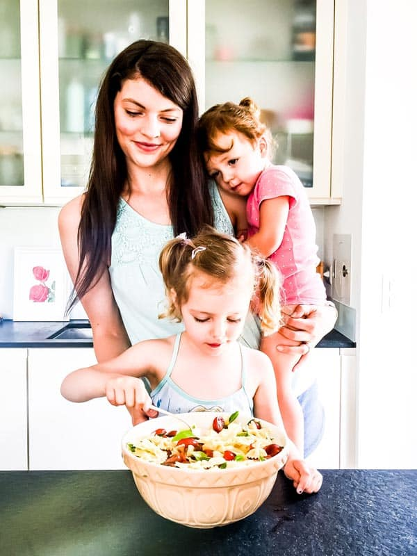 family making caprese pasta salad