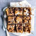 oatmeal cookie s'mores bars cut on a baking sheet with a knife