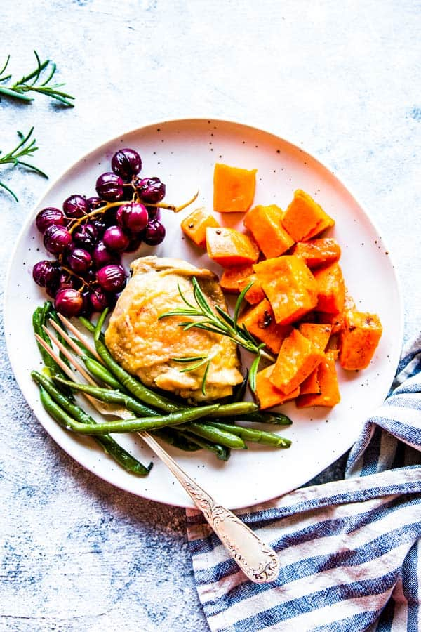 chicken, grapes, sweet potato and green beans on a white plate