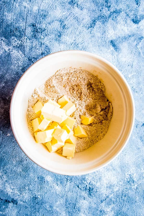 dry ingredients with butter in a bowl for a peach cobbler biscuit topping