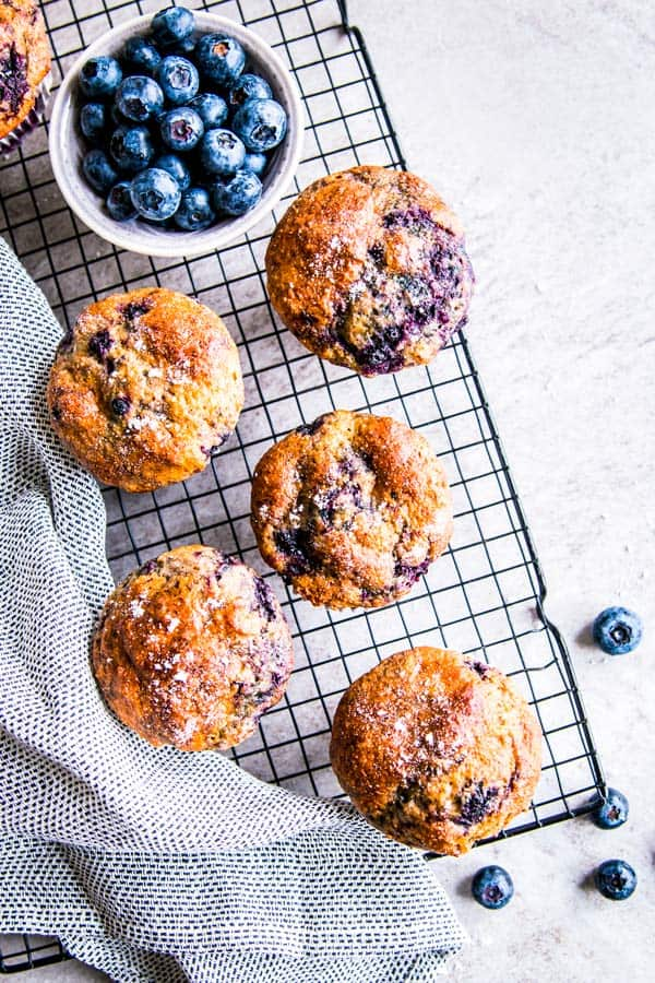 greek yogurt blueberry muffins on a cooling rack with fresh blueberries