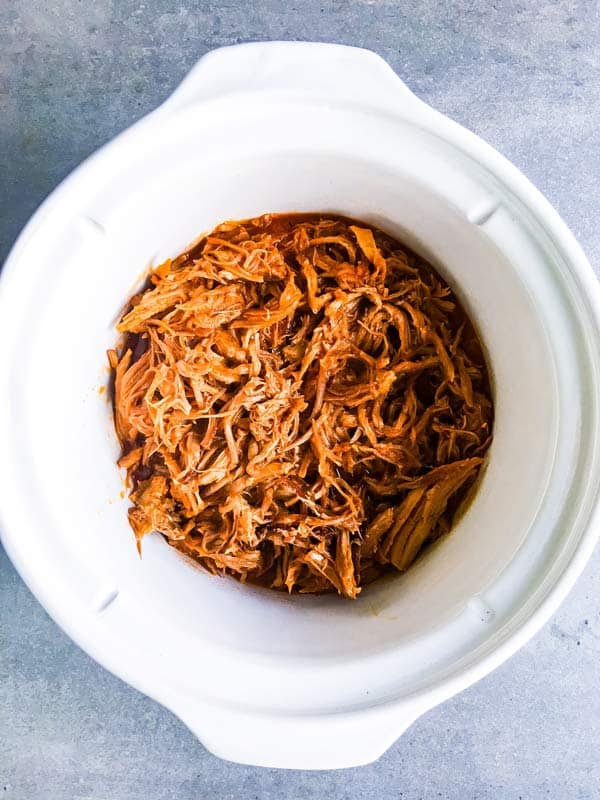 pineapple bbq pulled pork in a white crockpot