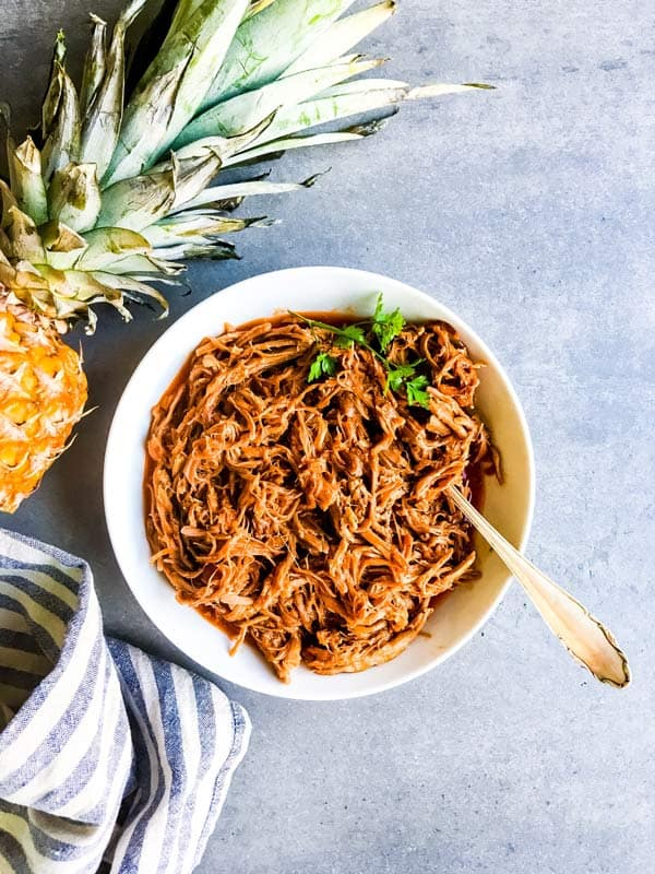 crockpot pineapple bbq pulled pork in a serving bowl with a fresh pineapple