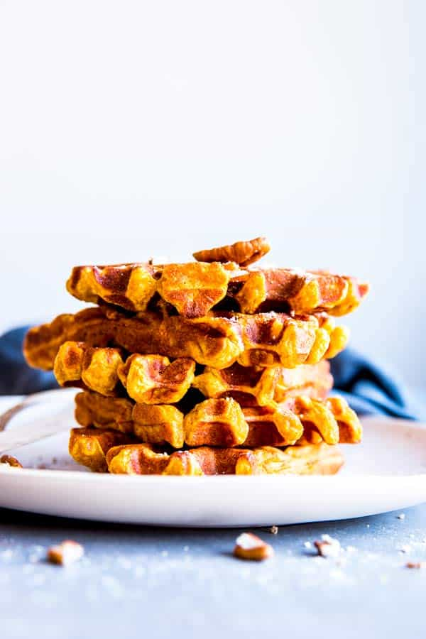stack pf pumpkin pecan waffles on a white plate