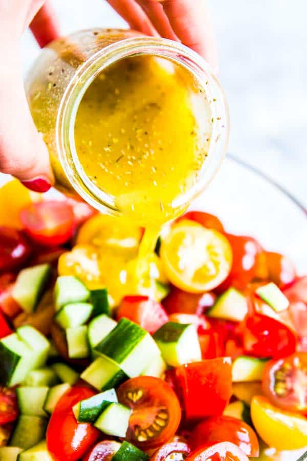pouring salad dressing on tomato cucumber salad