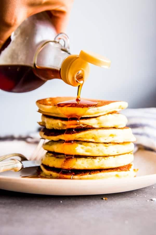 pouring maple syrup on a stack of buttermilk pancakes