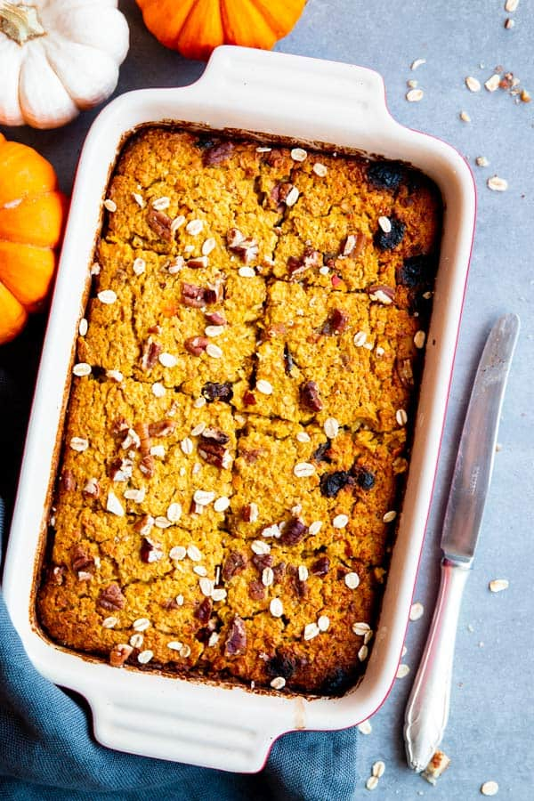 pumpkin baked oatmeal in a baking dish, with pumpkins around it
