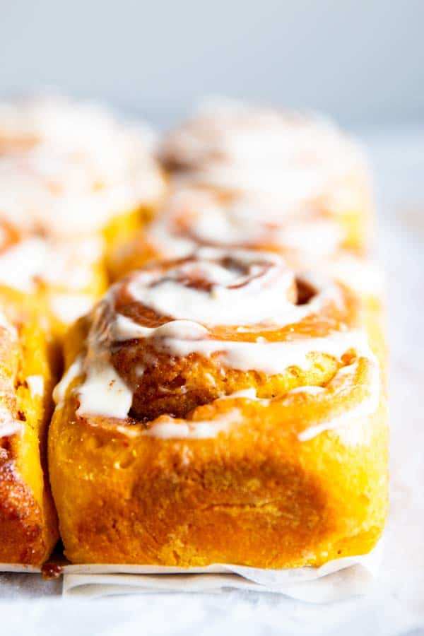 close up photo of pumpkin cinnamon rolls with frosting