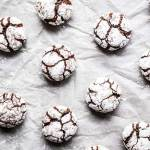 chocolate crinkle cookies on a piece of baking parchment