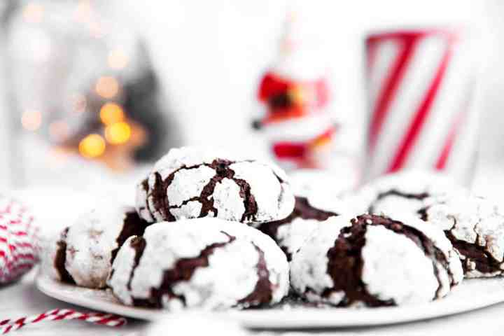 plate with chocolate crinkle cookies in front of Christmas ornaments