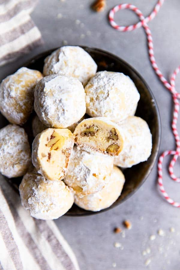 bowl of snowball cookies in a dark bowl