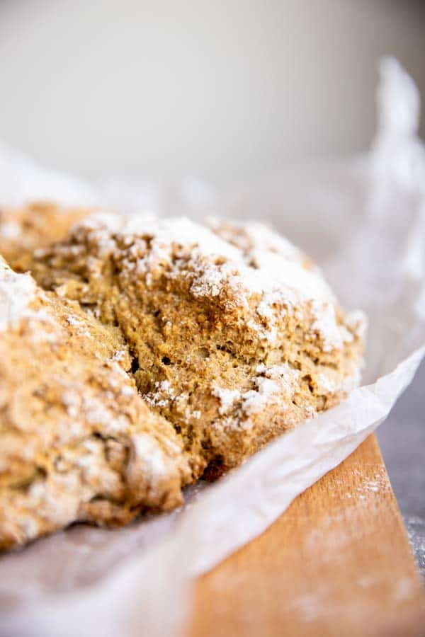 whole wheat Irish soda bread on a wooden board with baking parchment